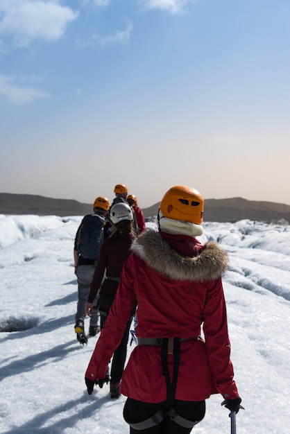 Group of people walking on the glacier trail in iceland Premium Photo