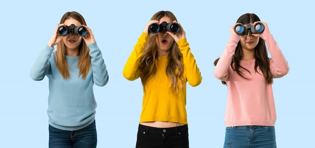 Group of people with colorful clothes and looking in the distance with binoculars Premium Photo