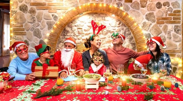 クリスマスフェストハウスパーティーで楽しんでいるサンタ帽子と幸せな家族の集合写真 Premium写真