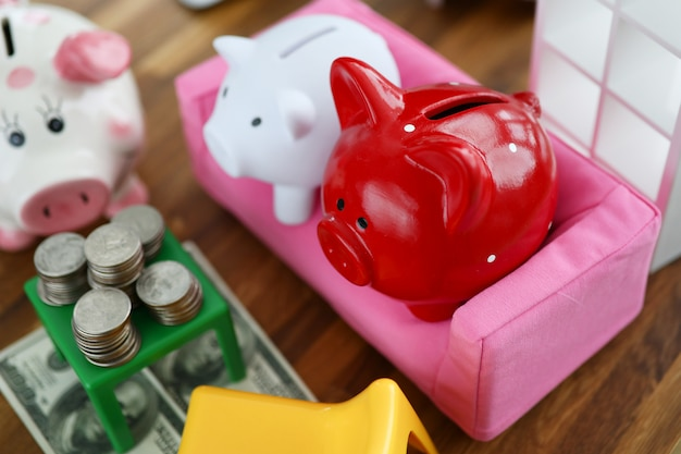 Group of piggy bank sit on sofa in house doll background Premium Photo