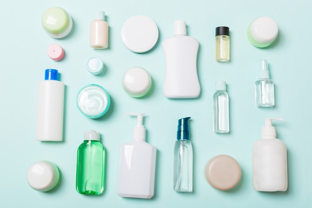 Group of plastic bodycare bottle flat lay composition with cosmetic products on blue Premium Photo