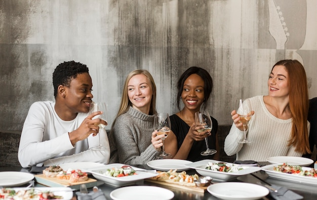 Group of positive people having dinner together Free Photo