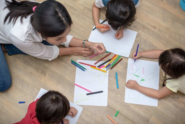 Group of preschool student and teacher drawing on paper in art class. Premium Photo