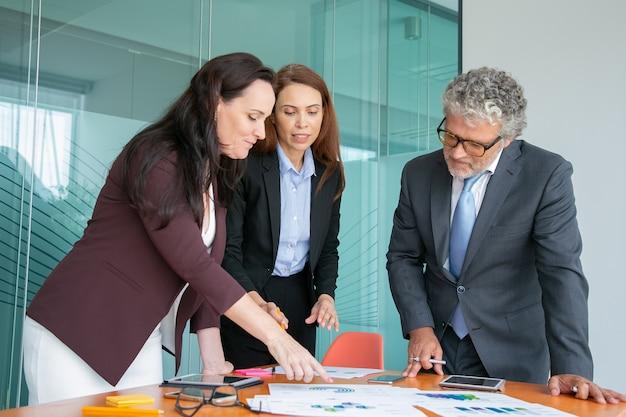 Gruppo di professionisti che analizzano rapporti cartacei con grafici e tabelle Foto Gratuite