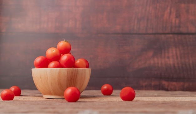 Group ripe tomato in a wood bowl place on the wooden table Premium Photo