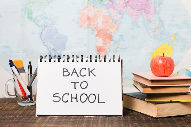 Group of school supplies with world map background Free Photo