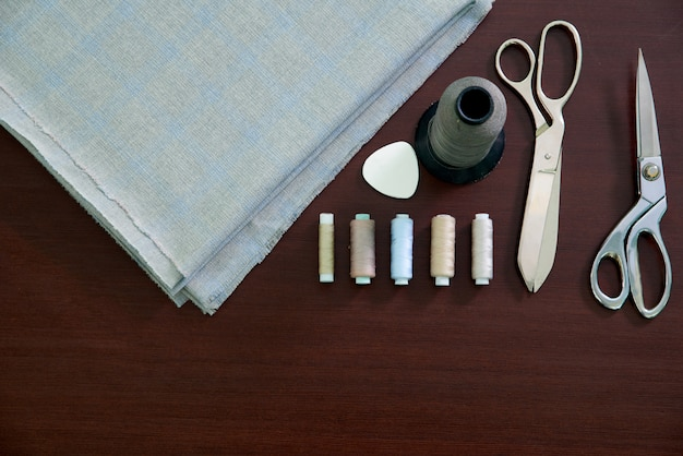 Group of sewing objects lying on a wooden table, flat lay concept of tailor shop Premium Photo