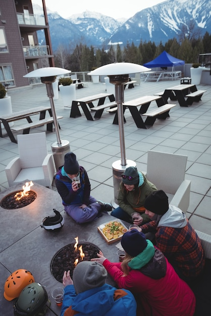 Group of skiers rubbing their hands near fireplace Free Photo