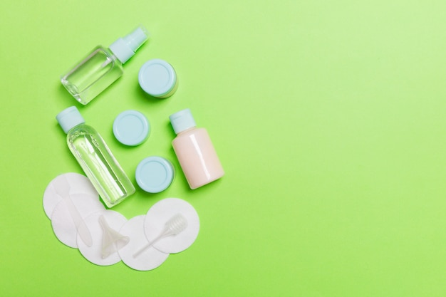 Group of small bottles for traveling on green background. copy space for your ideas. flat lay composition of cosmetic products. top view of cream containers with cotton pads Premium Photo