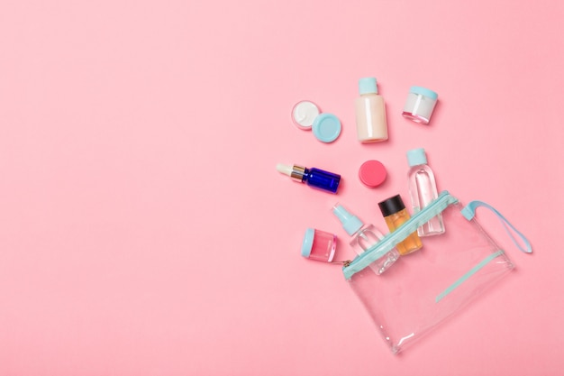 Group of small bottles for travelling on pink background. copy space for your ideas. flat lay composition of cosmetic products. top view of cream containers with cotton pads Premium Photo