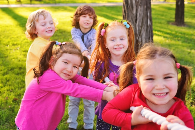 A group of small preschool children play a tug of war in the park. Premium Photo