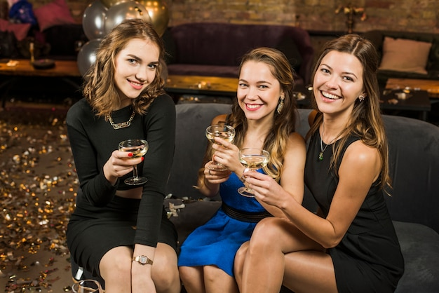 Group of smiling attractive female friends with a glass of drinks in party Free Photo