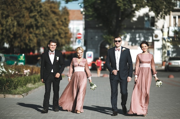 Group Of Smiling Groomsmen And Bridesmaids Walking Photo