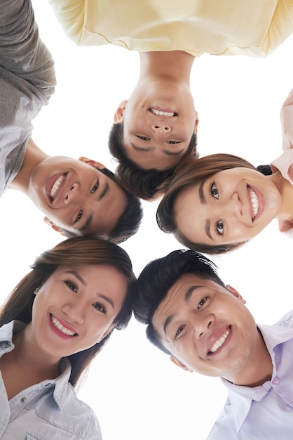 Group of smiling men and women looking at something together, shot from below Free Photo