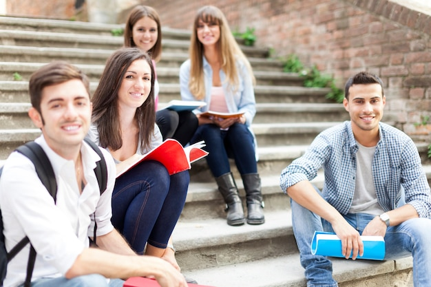 Group of smiling students sitting on a staircase Premium Photo