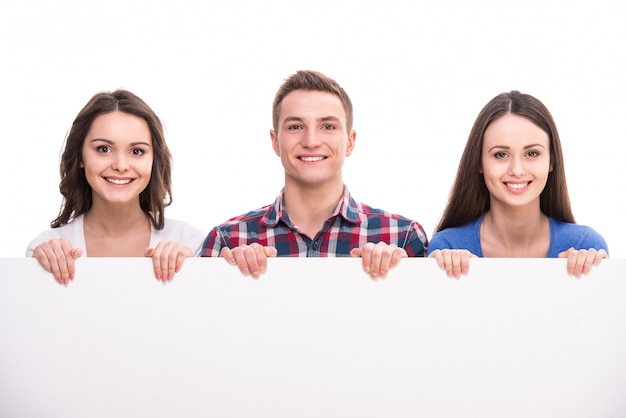 Group of smiling students with blank placard Premium Photo