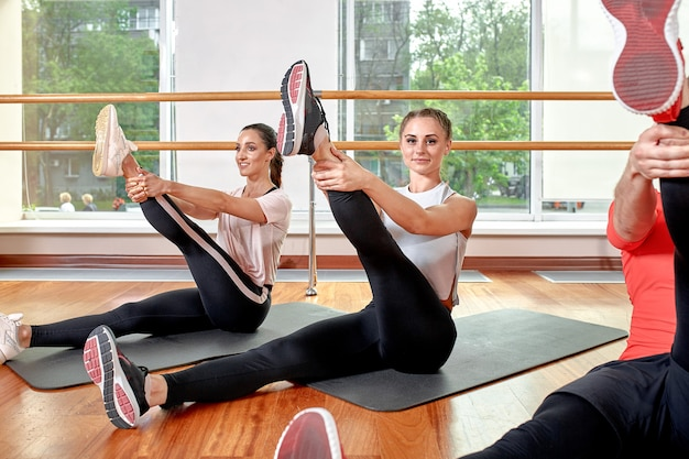 A group of sporting young people in sportswear, in a fitness room, doing push-ups or planks in the gym. Premium Photo