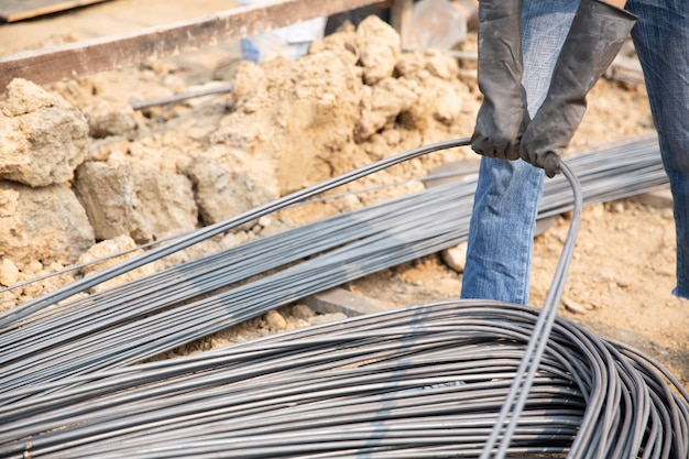 A group of steel rod tight by chain and lift up at construction site Free Photo