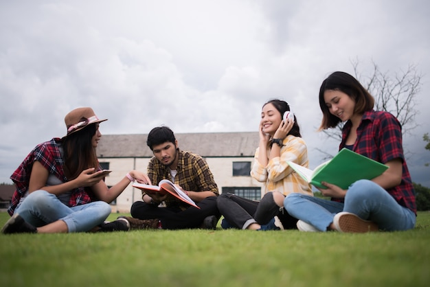 Group of student sitting at park after class. enjoy talking together. Free Photo