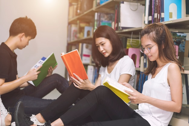 Group of students reading on floor in library. education concept. Premium Photo