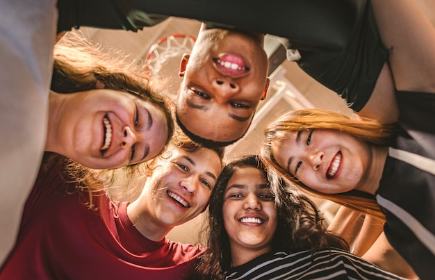 Group of teenager friends on a basketball court teamwork and togetherness concept Premium Photo