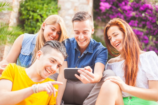 Group of teenagers laughing and looking at a smart phone Premium Photo