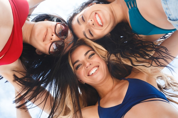 Group of three beautiful young girls having fun on the beach. close up picture of cheerful women from below. smiling company Premium Photo