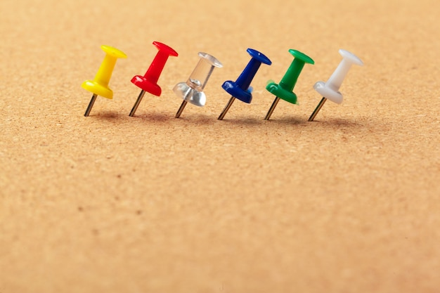 Group of thumbtacks pinned on corkboard in a row close up view Premium Photo