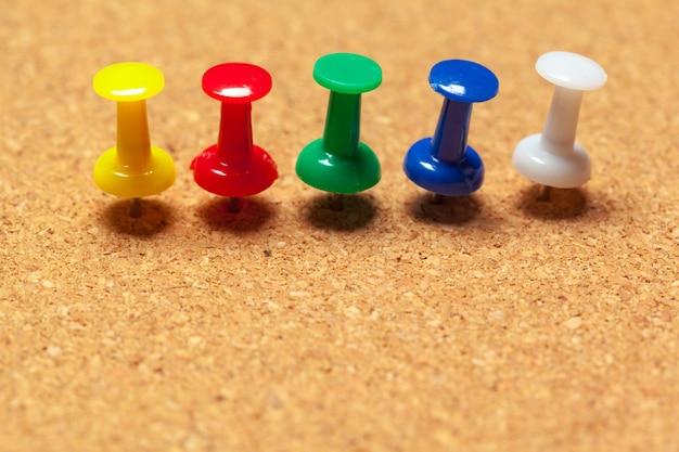 Group of thumbtacks pinned on corkboard in rows Premium Photo
