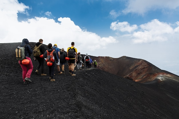 Group of tourists hiking on top of the etna volcano in sicily, italy Free Photo