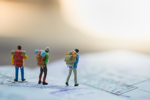 Group of traveler miniature figures with backpack walking on passport with immigration stamps. Premium Photo