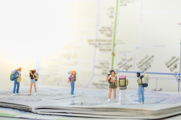 Group of traveler miniature mini figures with backpack standing Premium Photo