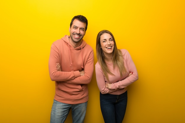 Group of two people on yellow background keeping the arms crossed while smiling Premium Photo