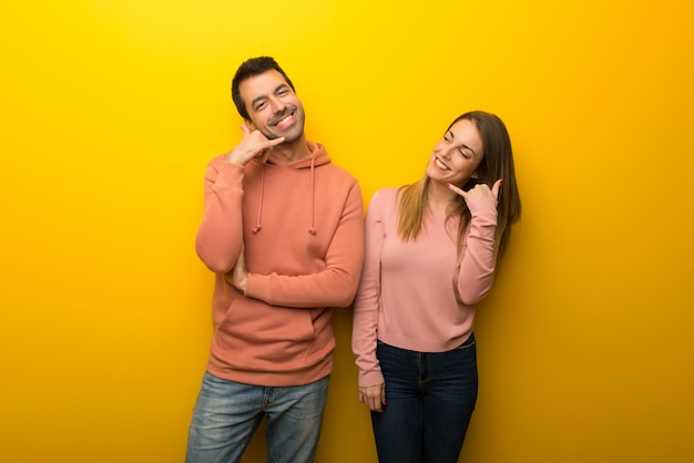 Group of two people on yellow background making phone gesture. call me back sign Premium Photo