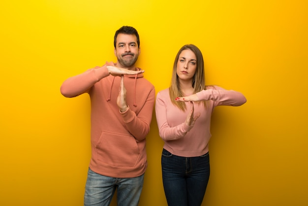 Group of two people on yellow background making stop gesture Premium Photo