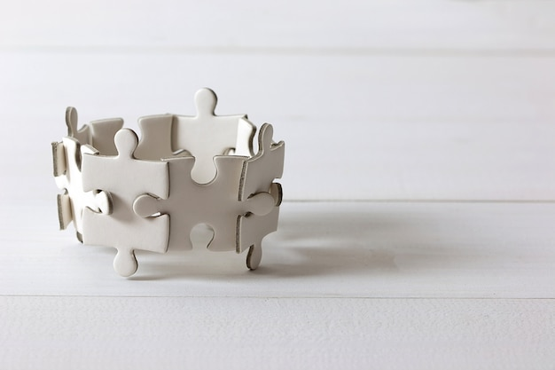 Group of white jigsaw puzzle on wooden table. business teamwork and collaborate  concept. Premium Photo