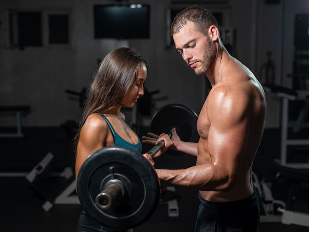 Group with dumbbell weight training equipment on sport gym. Premium Photo