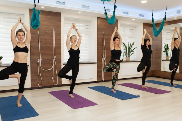 Group of womans doing yoga exercises in gym. fit and wellness lifestyle Premium Photo