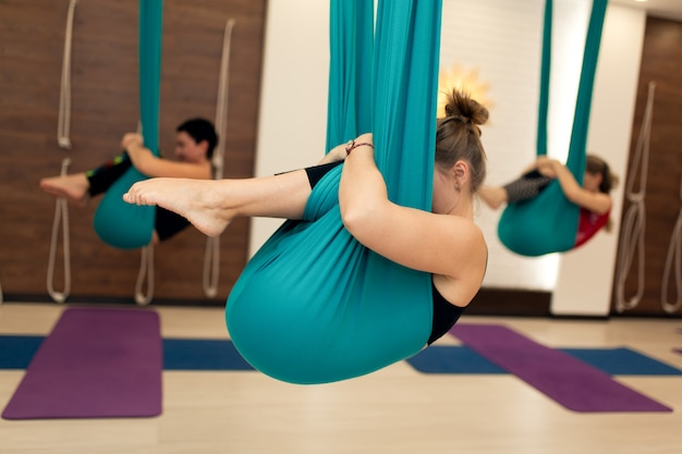 A group of women are hanging in a fetal position in a hammock. fly yoga class in the gym Premium Photo