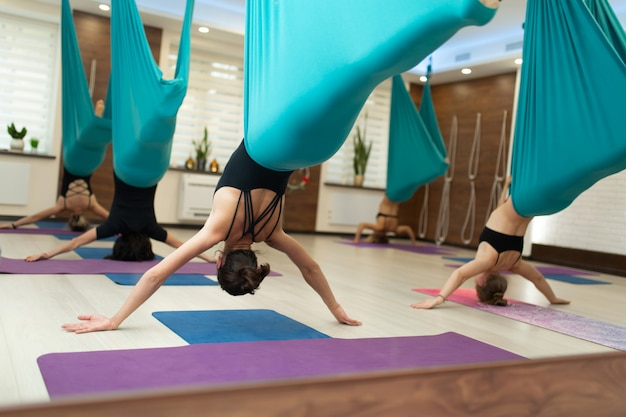 A group of women hang upside down in a hammock. fly yoga class in the gym Premium Photo