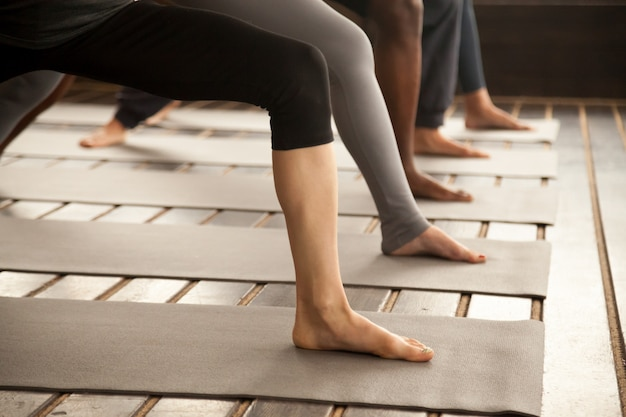 Group of yogi people in warrior two legs close up Free Photo