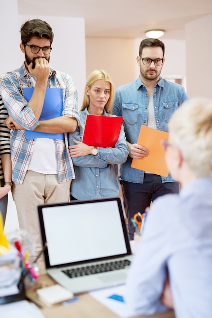 Group of young afraid people waiting in the row with folders for a job interview and listening for instruction. Premium Photo