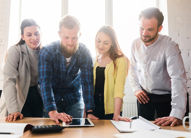 Group of young businesspeople looking at digital tablet on desk in office Free Photo