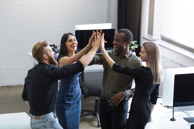 Group of young colleagues giving each other a high five Free Photo
