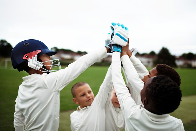Group of young cricketers doing a high five Premium Photo