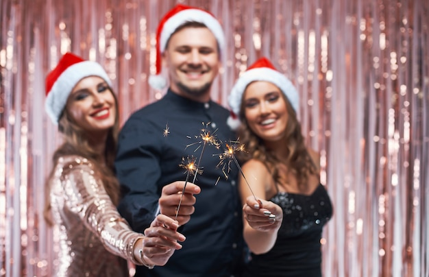 Group of young friends enjoying new year celebration with sparkles in hands. Premium Photo