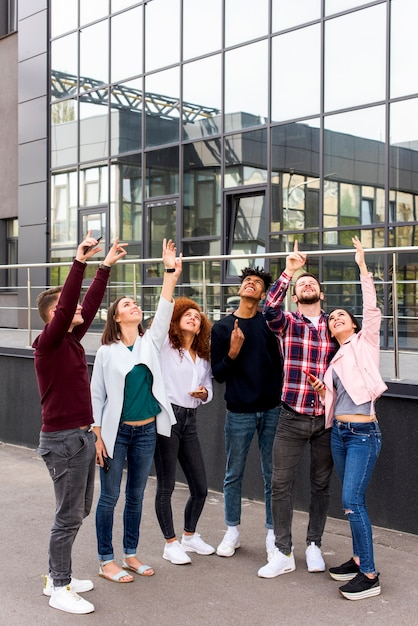 Group of young friends standing on street pointing upward in front of modern building Free Photo