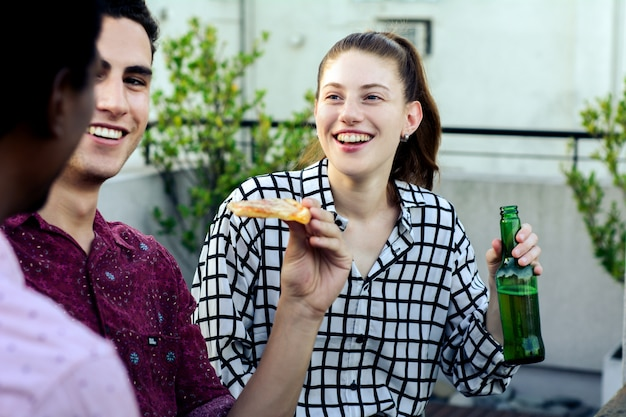 Group of young friends with pizza and bottles of drink Premium Photo