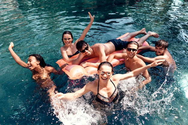 Group of young happy people having fun in pool Premium Photo