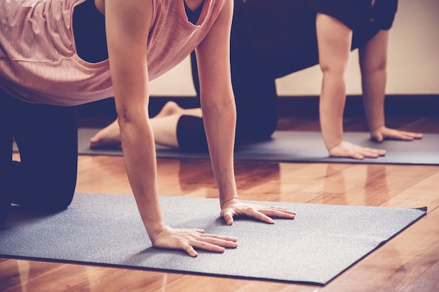 Group of young healthy asian women practicing yoga  lesson with instructor in home studio Premium Photo